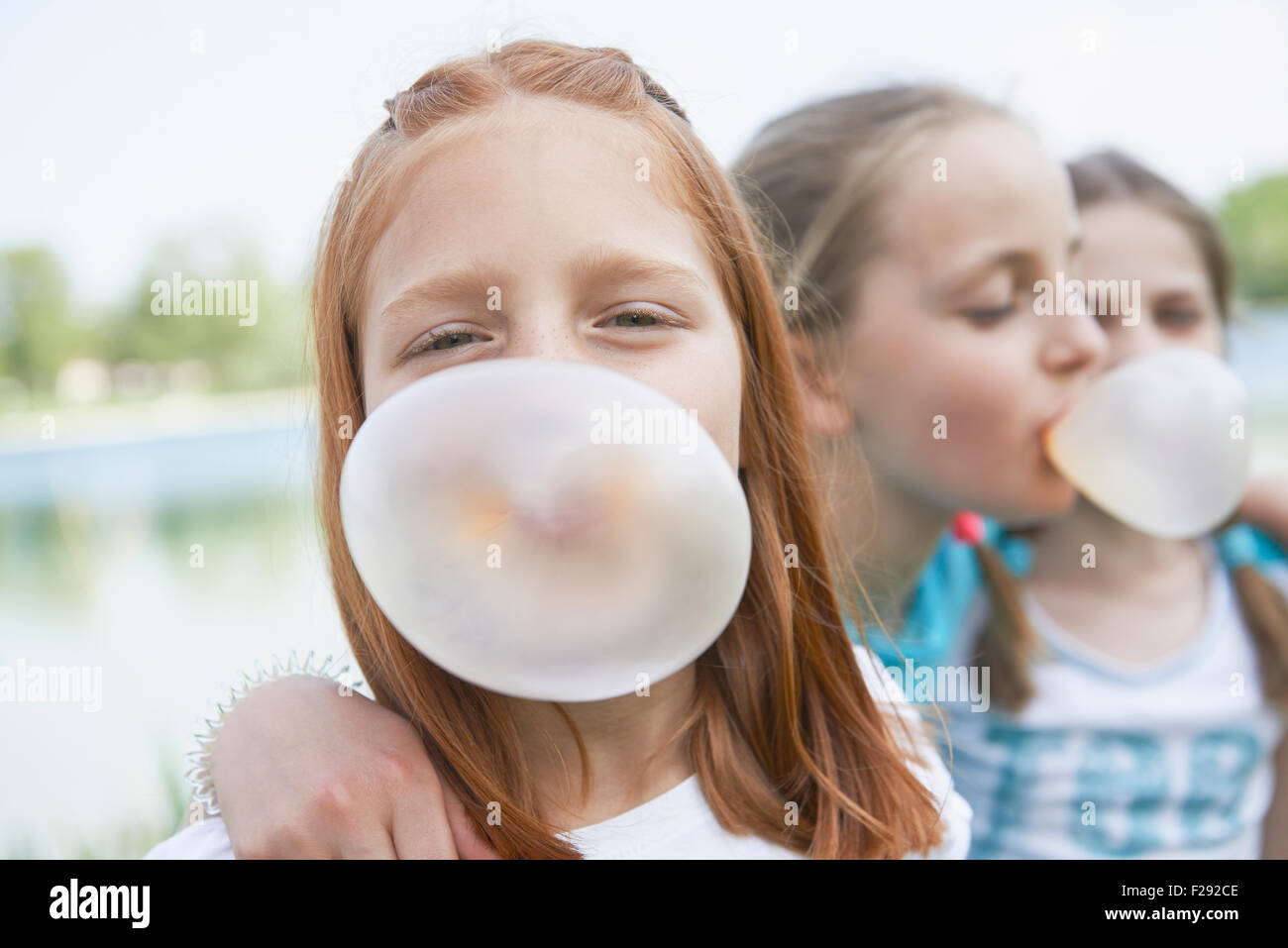Girls blowing chewing gum bubbles, Bavaria, Germany - Stock Image
