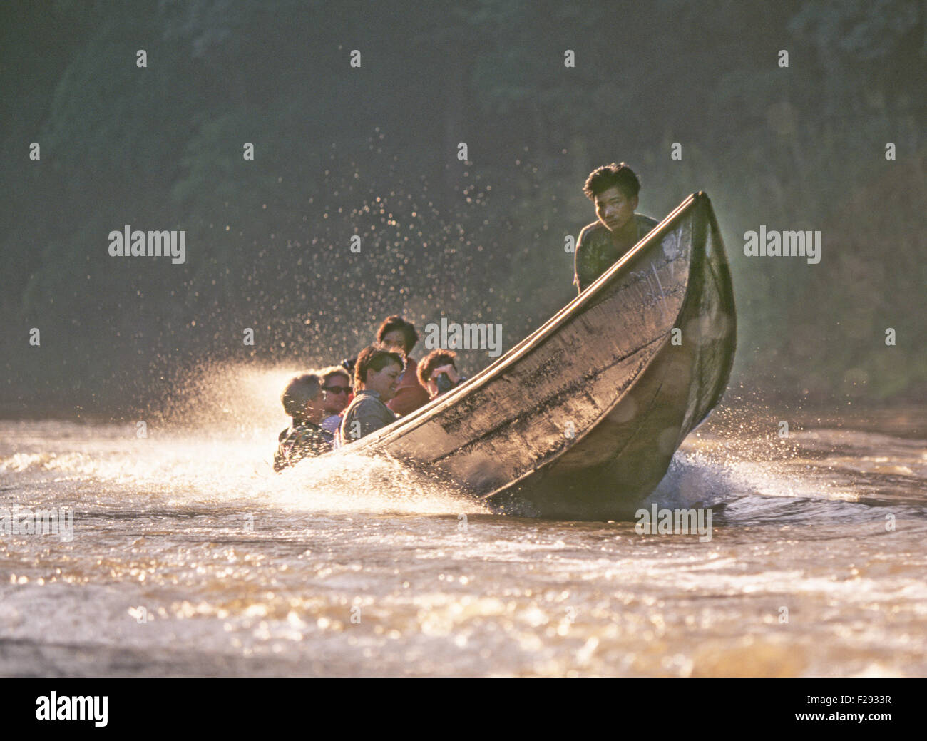 Thai boatmen carry tourists up the Ping River in a tiger-tailed boat near the city of Chaing Mai, northern Thailand, - Stock Image