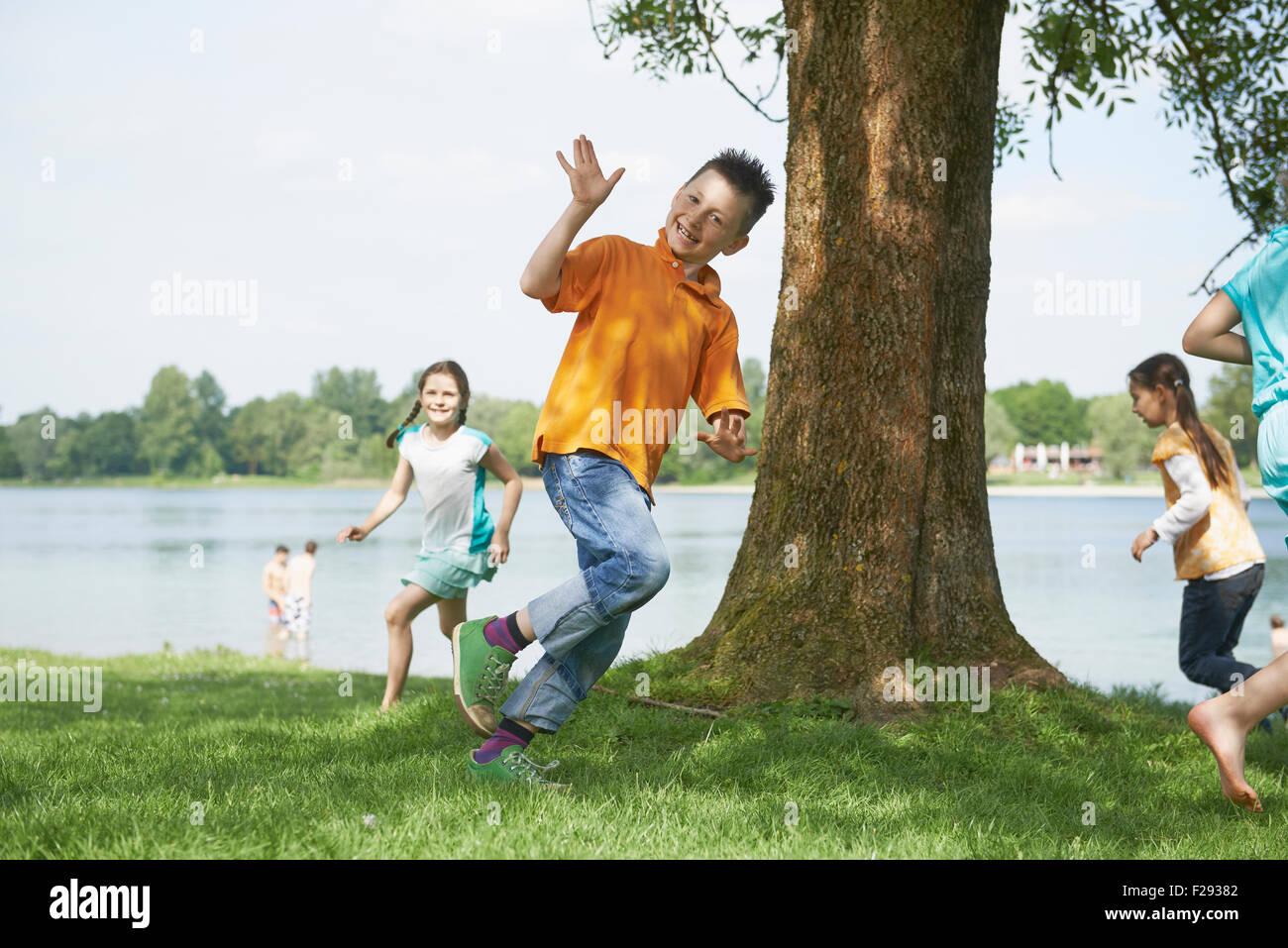 Children running around a tree at lakeshore, Bavaria, Germany - Stock Image