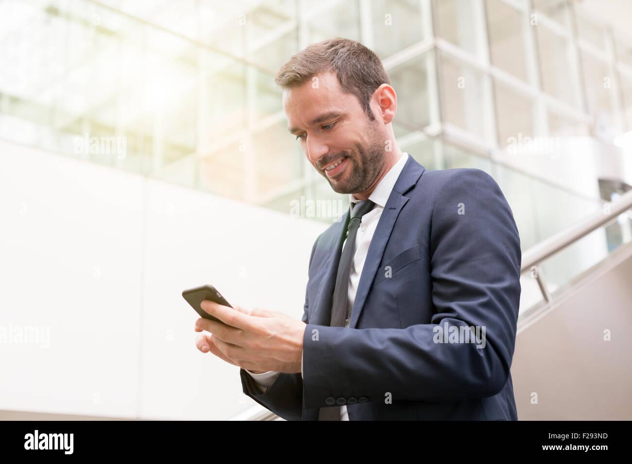 Businessman sending a SMS - Stock Image