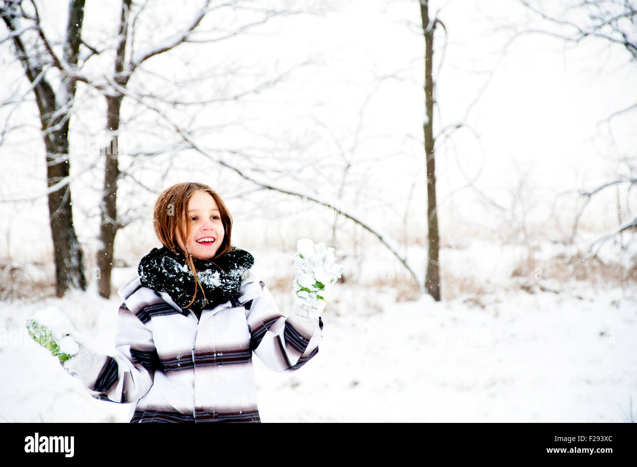 Girl holding snowball to throw - Stock Image