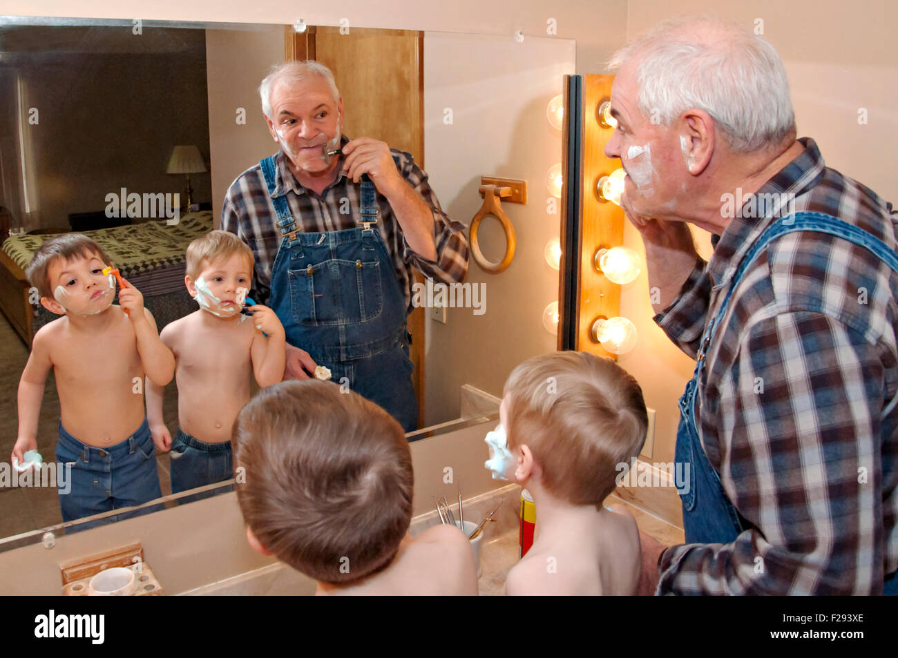 Grandfather teaching grandsons to shave - Stock Image