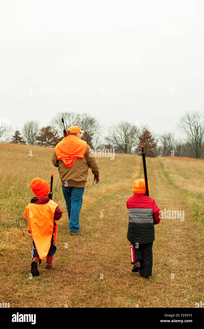 boys carrying toy firearms in practice deer hunt Stock Photo