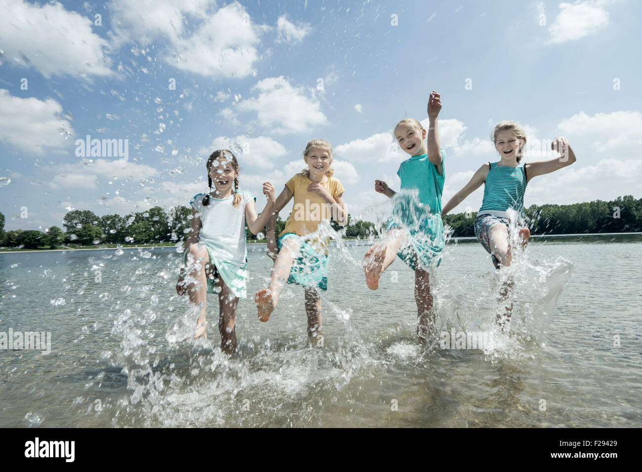 Group of friends splashing water in the lake, Bavaria, Germany - Stock Image