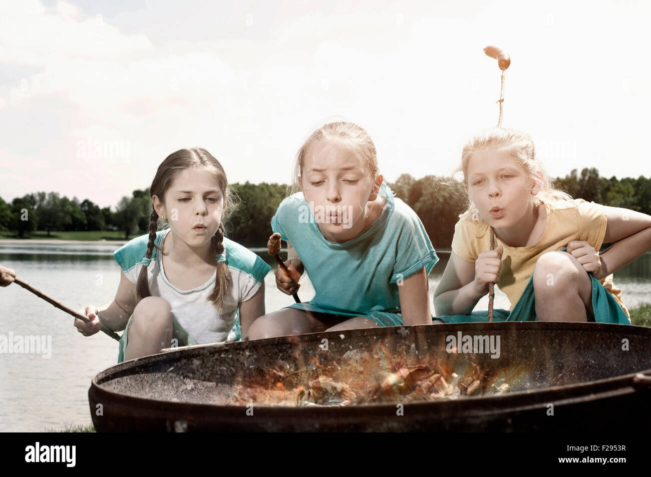 Three friends preparing sausages on campfire, Bavaria, Germany - Stock Image