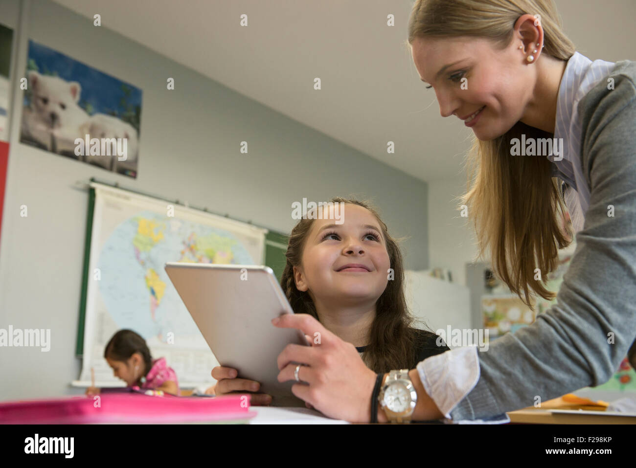 Female teacher showing a girl something on digital tablet pc in classroom, Munich, Bavaria, Germany - Stock Image