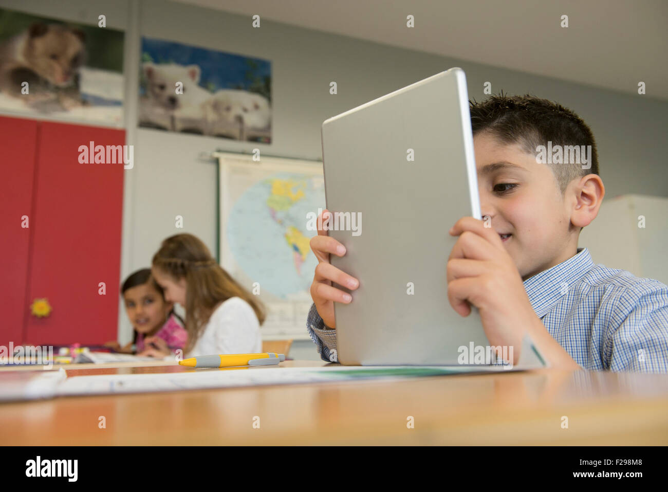 Schoolboy using a digital tablet in classroom, Munich, Bavaria, Germany - Stock Image