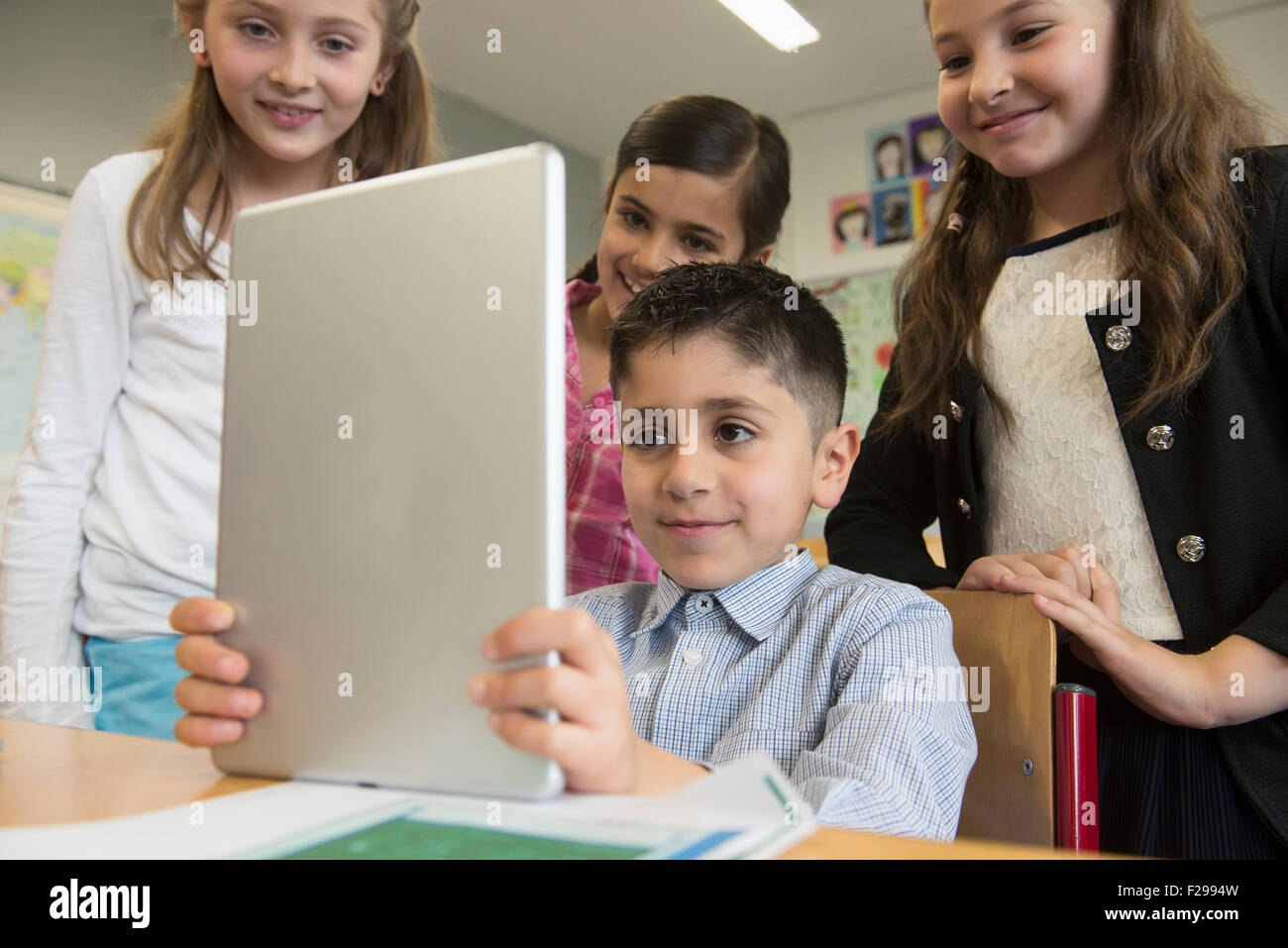 School children using a digital tablet in classroom, Munich, Bavaria, Germany - Stock Image