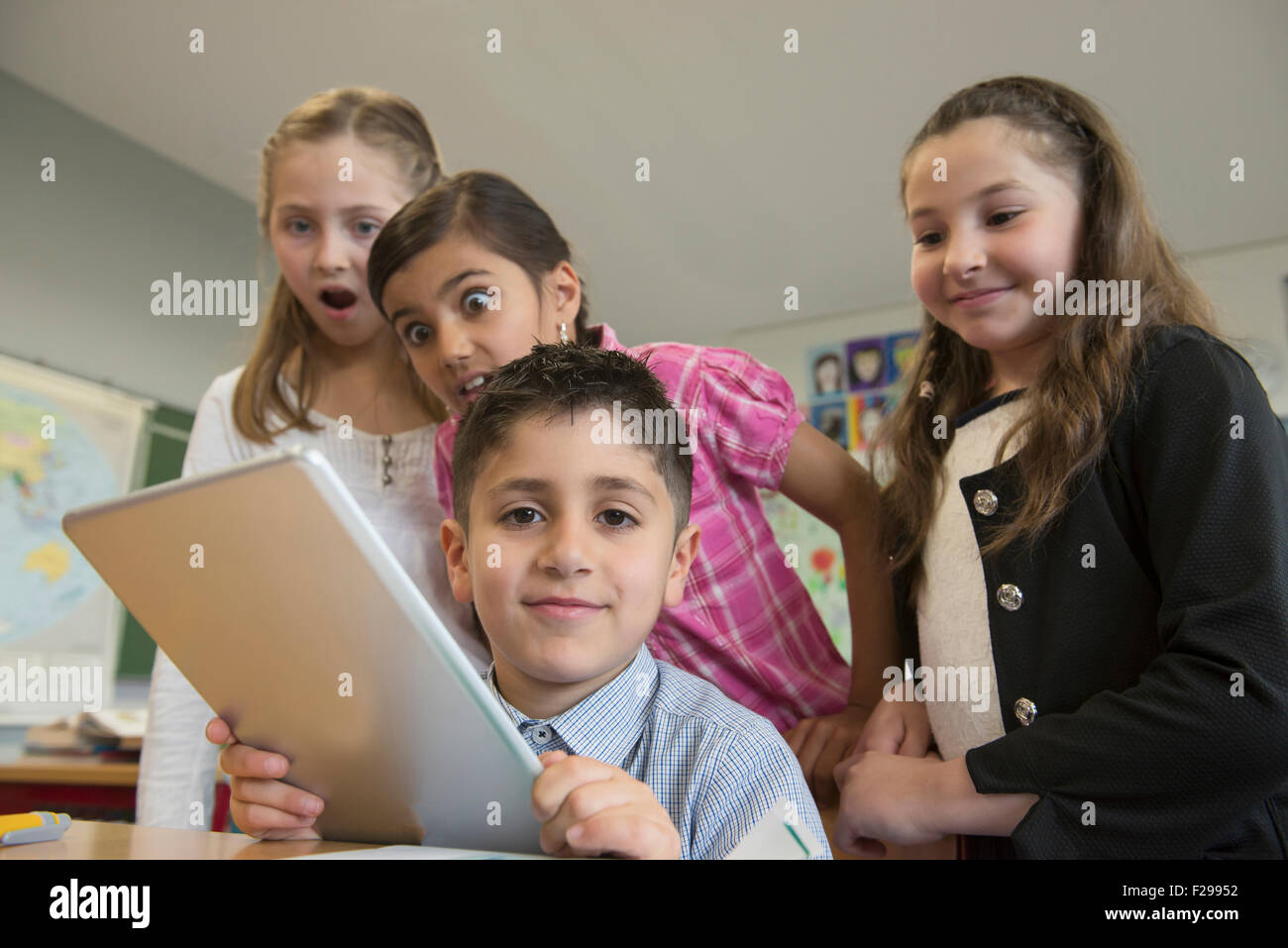 School children using a digital tablet in a classroom, Munich, Bavaria, Germany - Stock Image