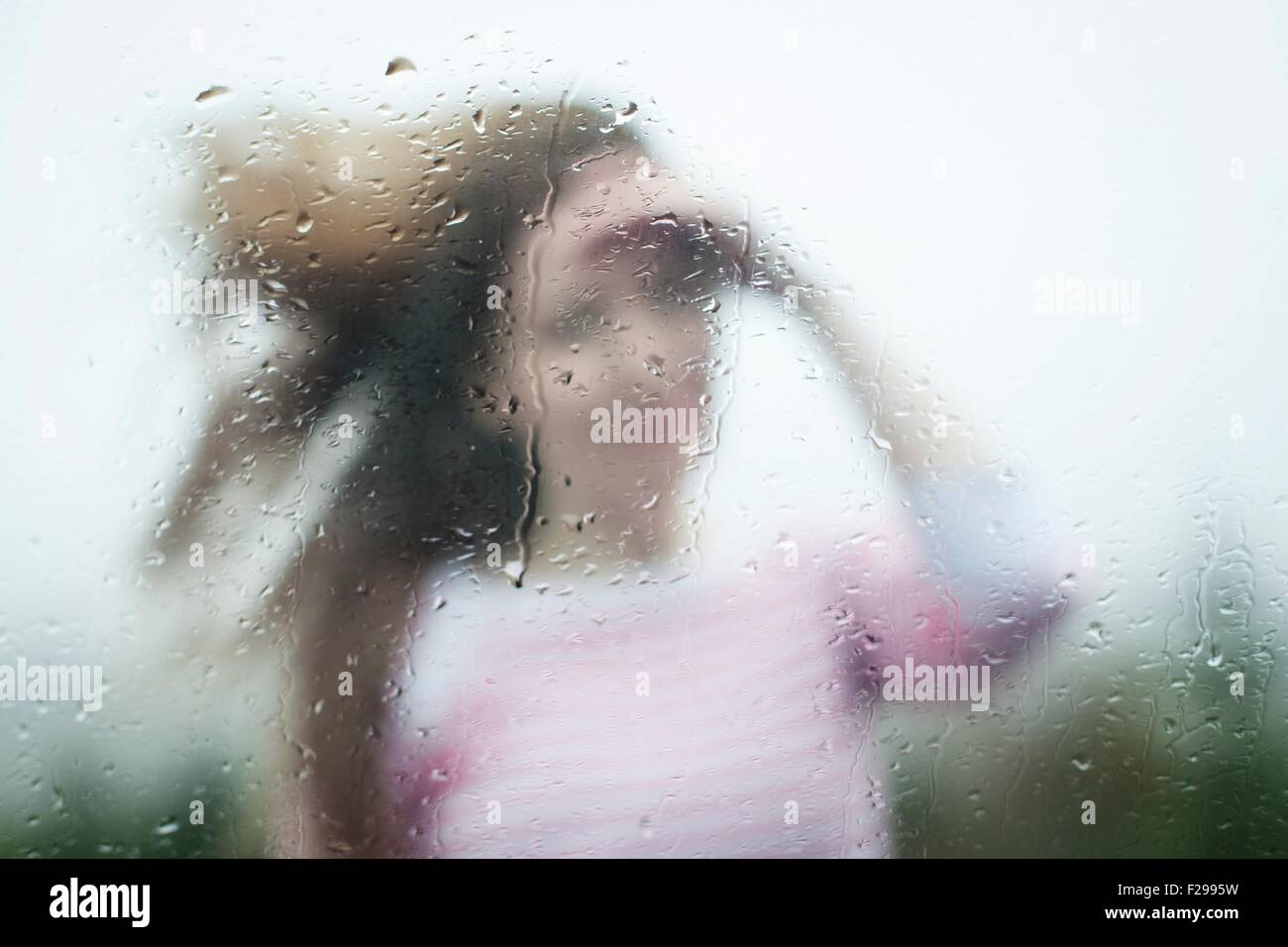 Blurry image of a woman through a rainy window - Stock Image
