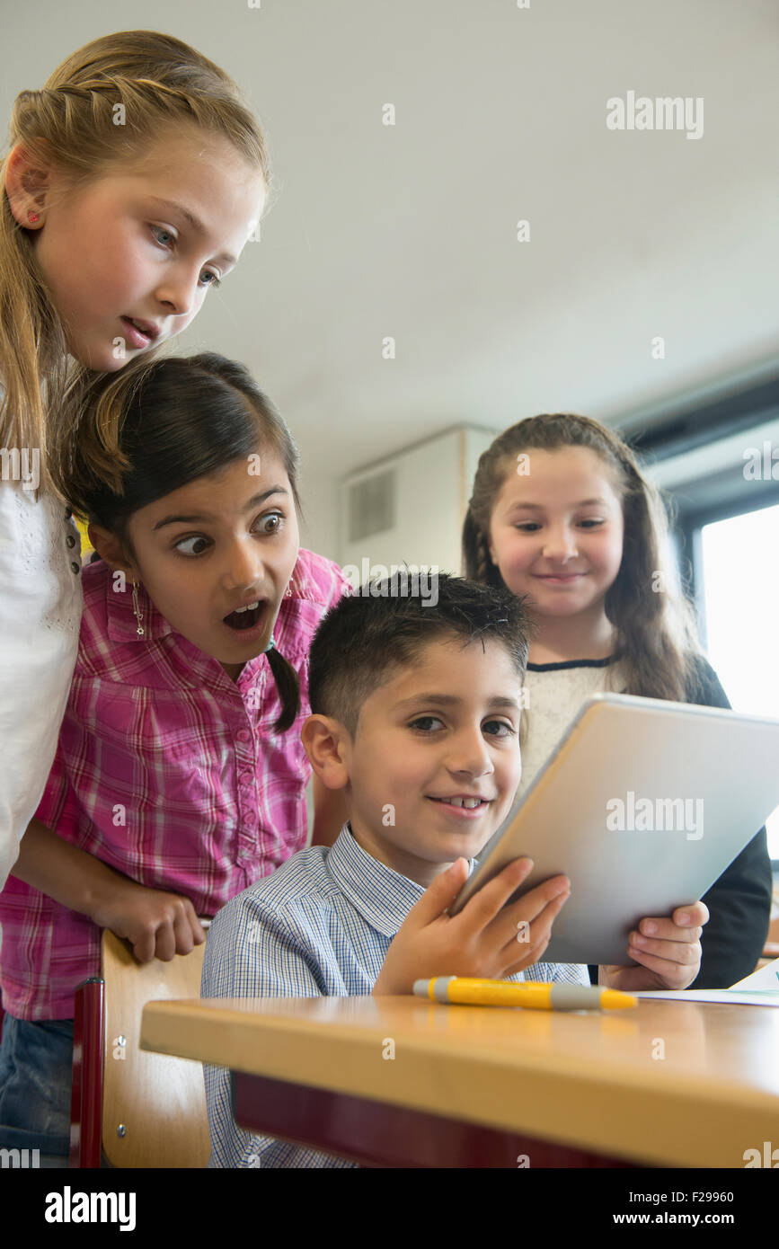 School children using a digital tablet in a classroom, Munich, Bavaria, Germany, - Stock Image