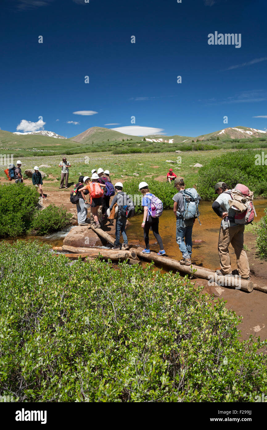 Georgetown, Colorado - Teenage members of a trail maintenance crew cross a stream on a mountain trail. - Stock Image
