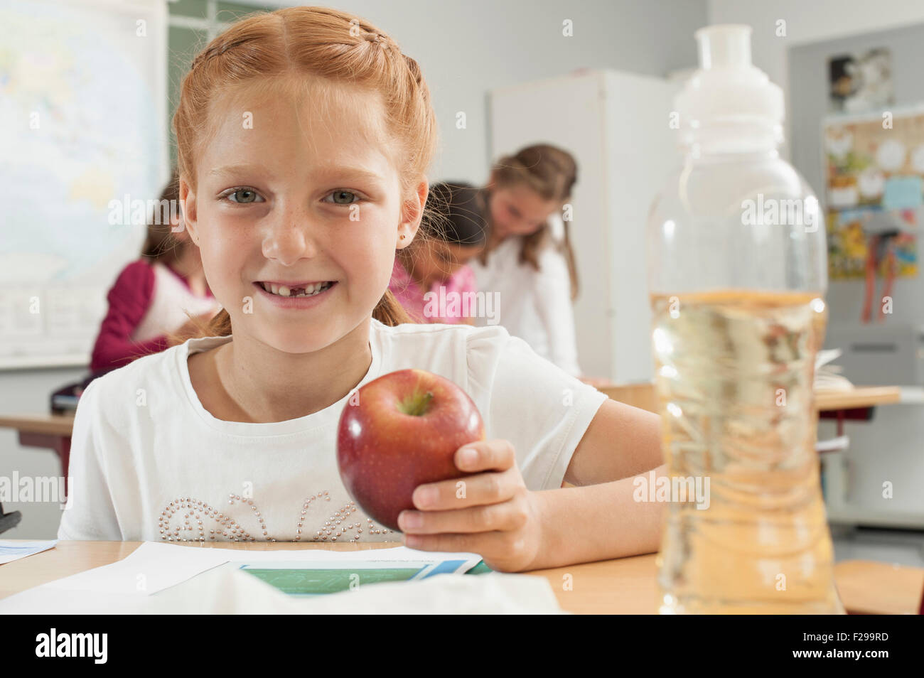 Portrait of a schoolgirl holding an apple in classroom, Munich, Bavaria, Germany - Stock Image