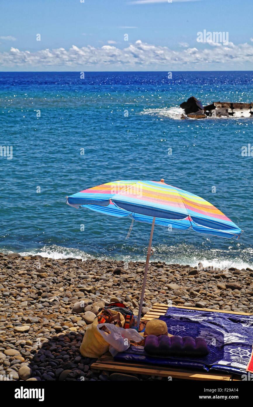 Colourful scene at a stony beach, parasol and dark blue sea at Madeira, Portugal - Stock Image