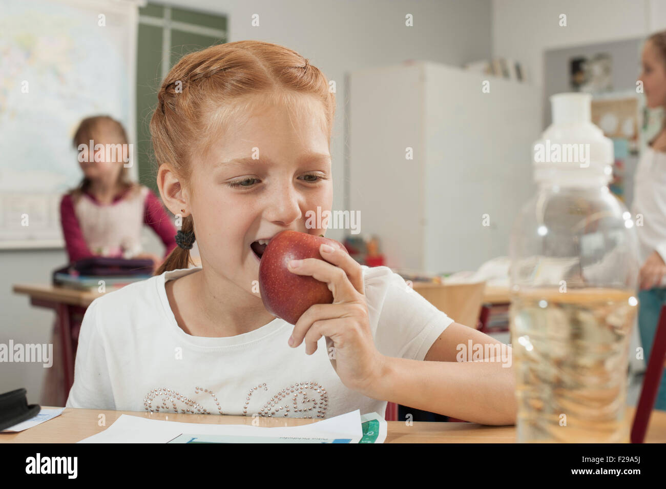 Close-up of a schoolgirl eating an apple in classroom, Munich, Bavaria, Germany - Stock Image