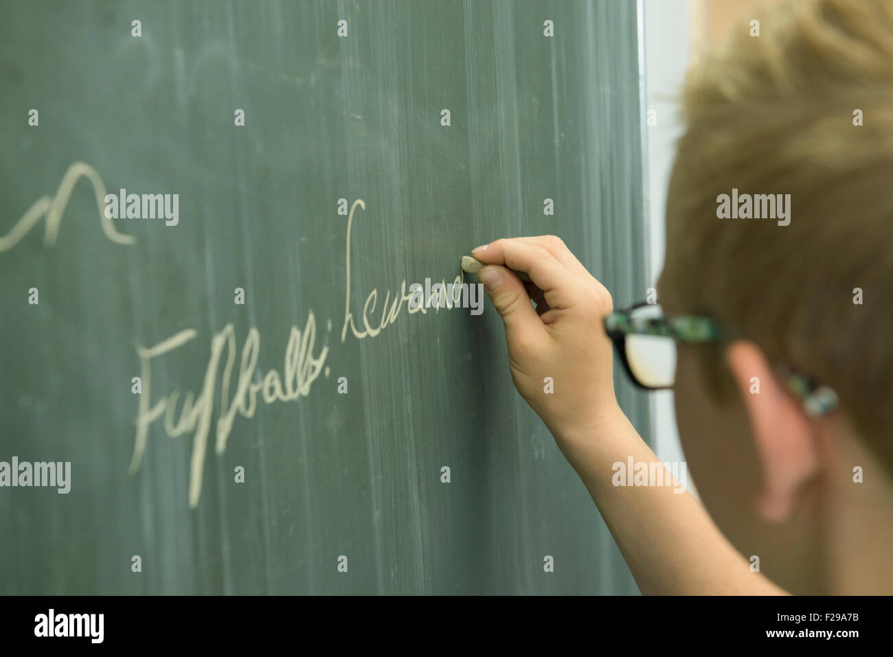 Schoolboy writing on blackboard in classroom, Munich, Bavaria, Germany - Stock Image