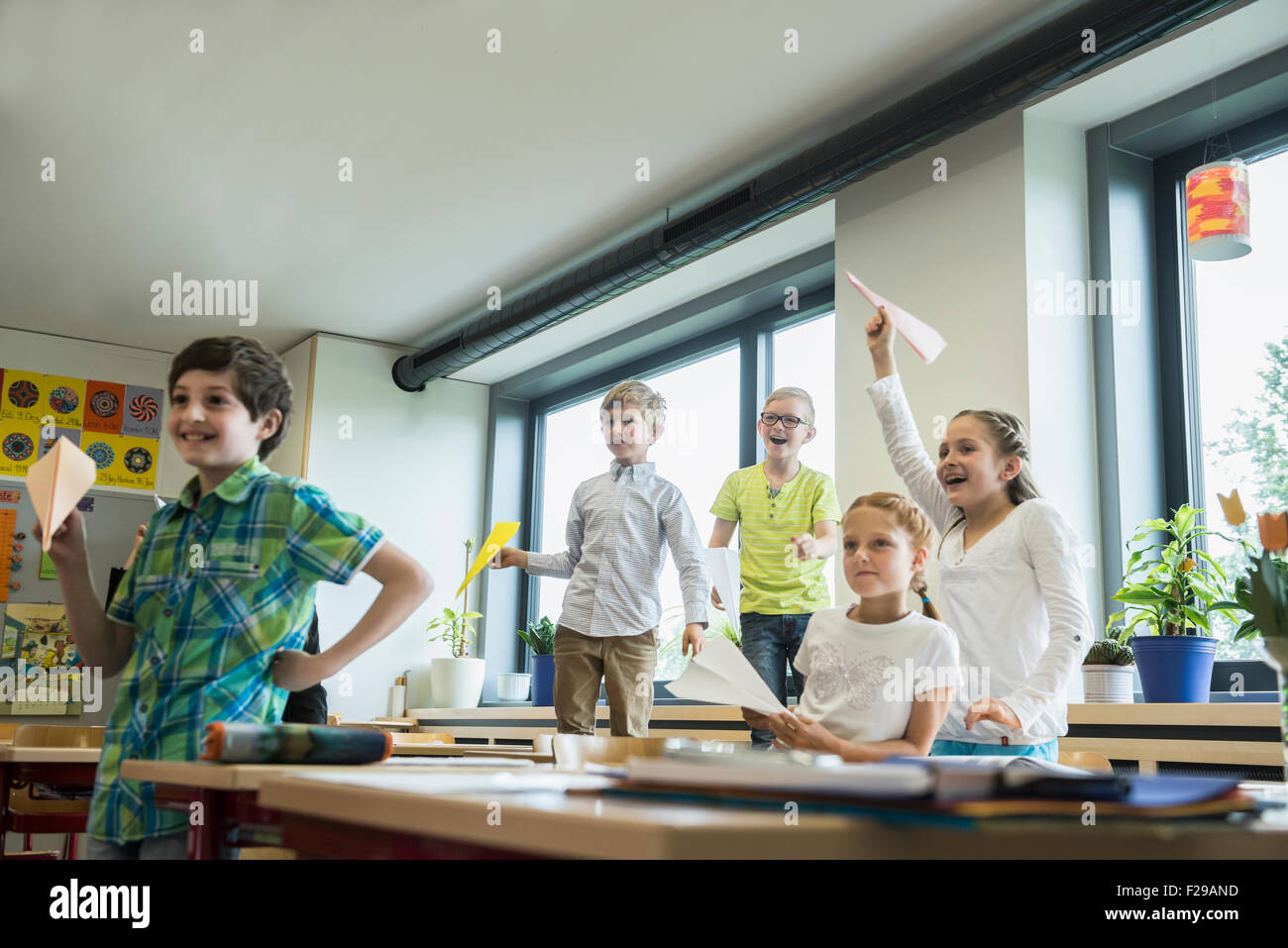 School children playing with paper airplanes in classroom, Munich, Bavaria, Germany Stock Photo