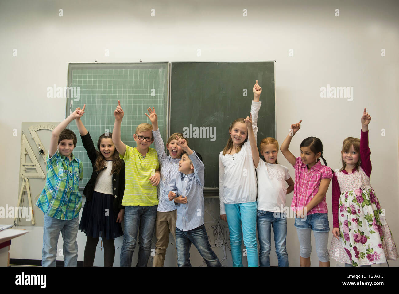 School students raising hands in front of blackboard in classroom, Munich, Bavaria, Germany - Stock Image