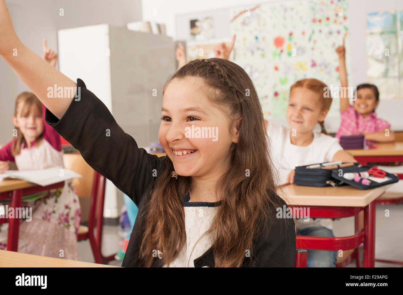 School children with raised hands in classroom, Munich, Bavaria, Germany - Stock Image