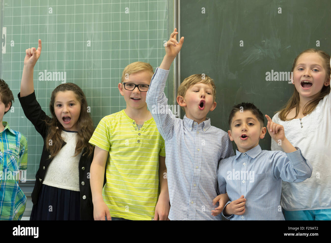 School students raising hands in front of blackboard in classroom, Munich, Bavaria, Germany, - Stock Image