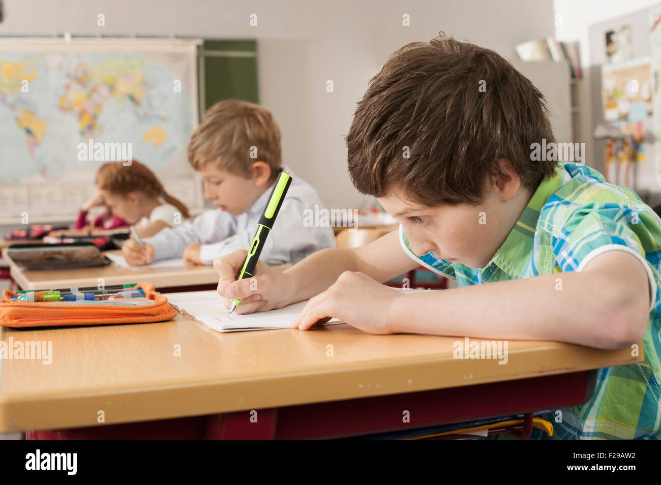 School students writing in notebooks, Munich, Bavaria, Germany - Stock Image