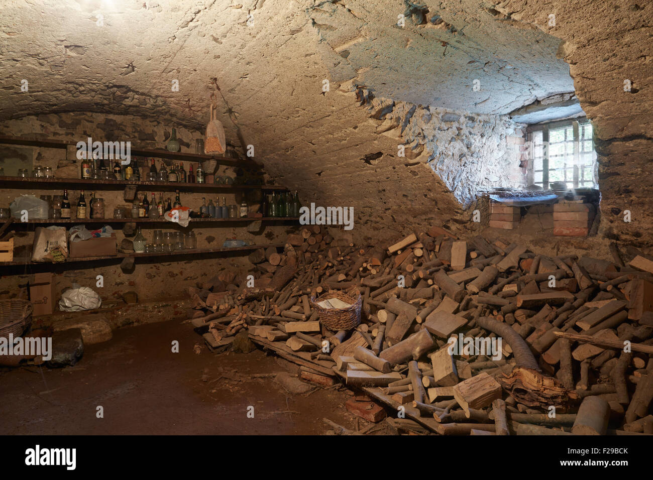 Old, dark basement with wood pile in ancient house - Stock Image