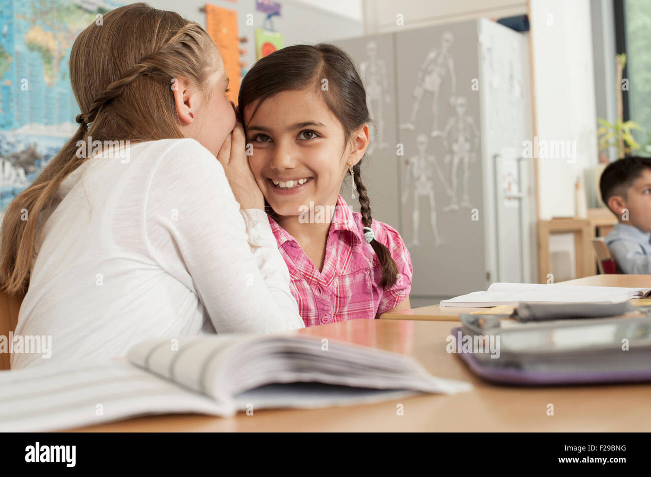 Schoolgirls whispering in class, Munich, Bavaria, Germany - Stock Image