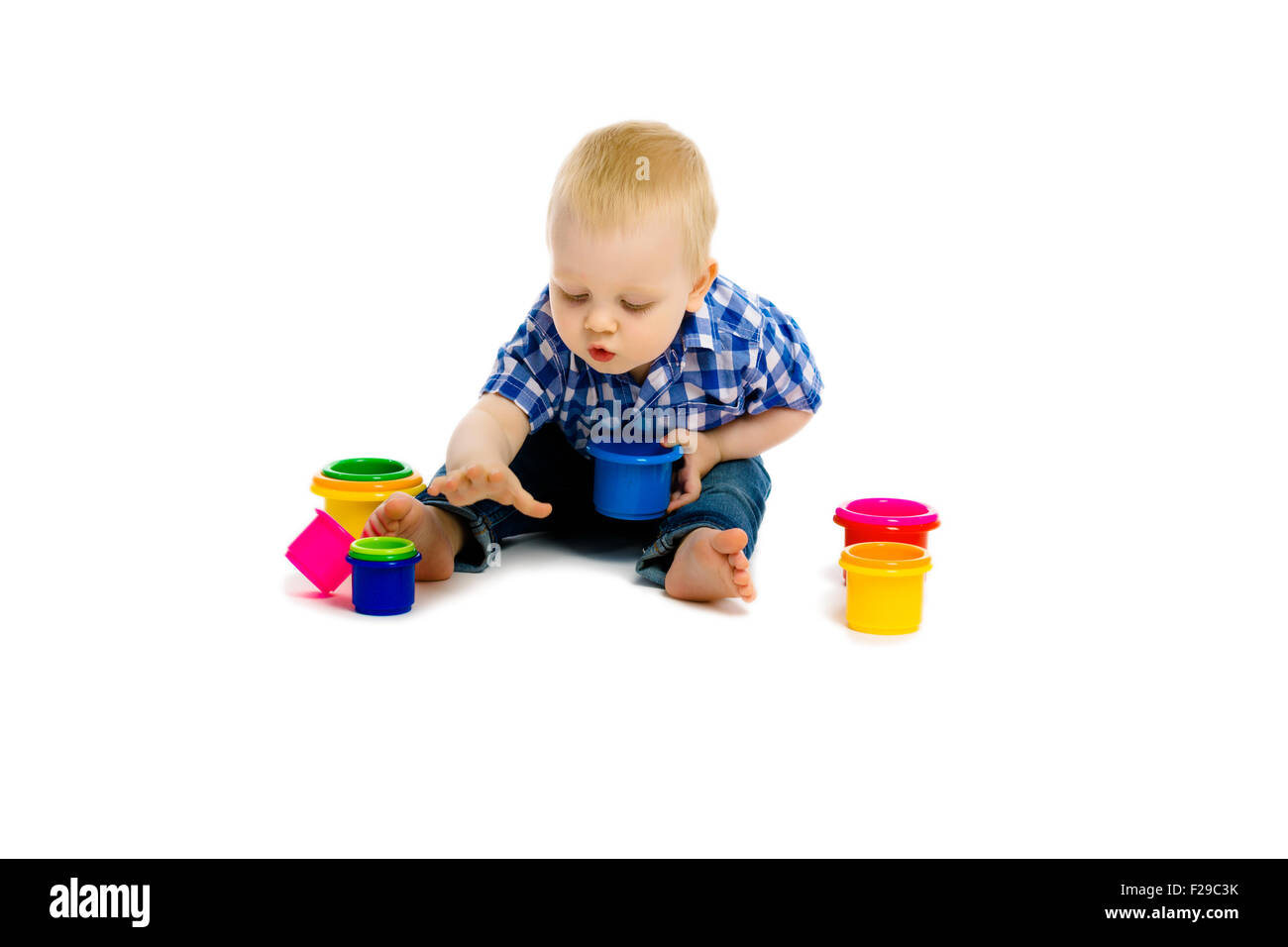 baby boy sitting on a white floor with toys - Stock Image