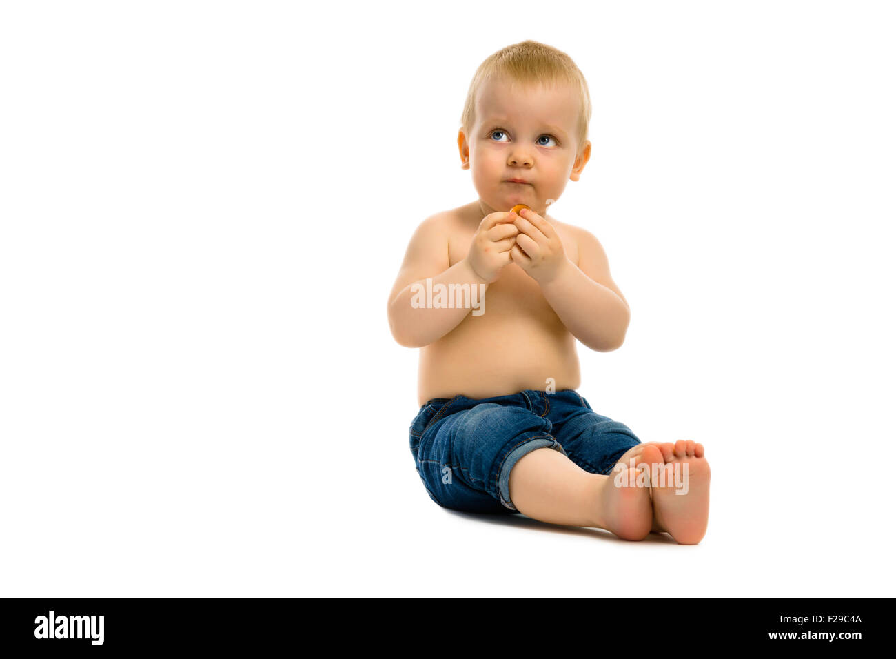 baby boy sitting on a white floor - Stock Image