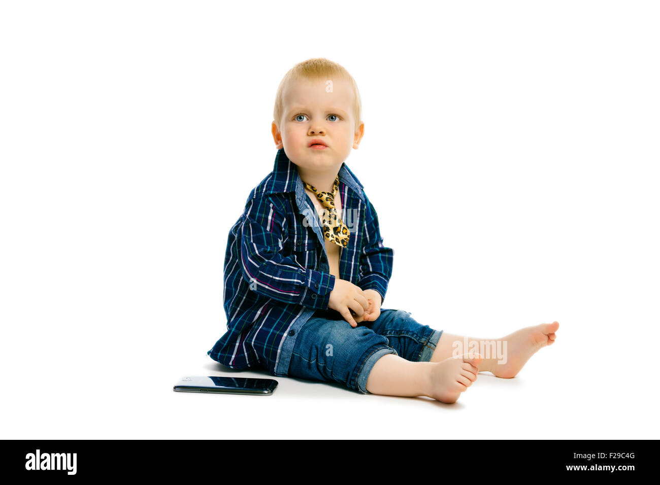 baby boy in a tie sitting on a white floor - Stock Image