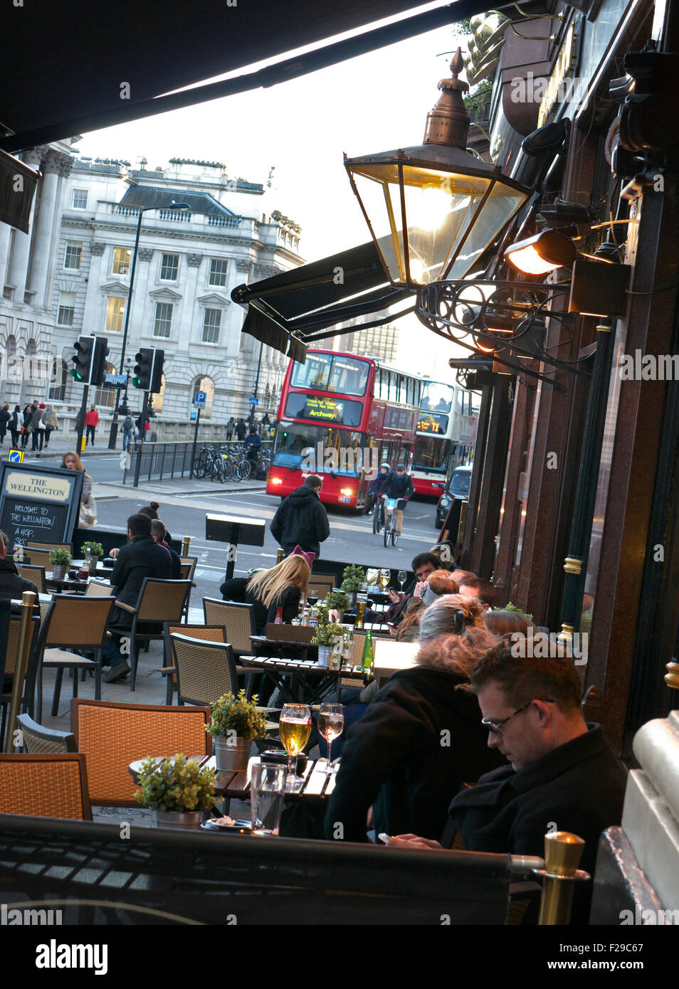 Busy central London scene at dusk with red bus cyclist commuters and typical real ale pub in foreground The Strand - Stock Image