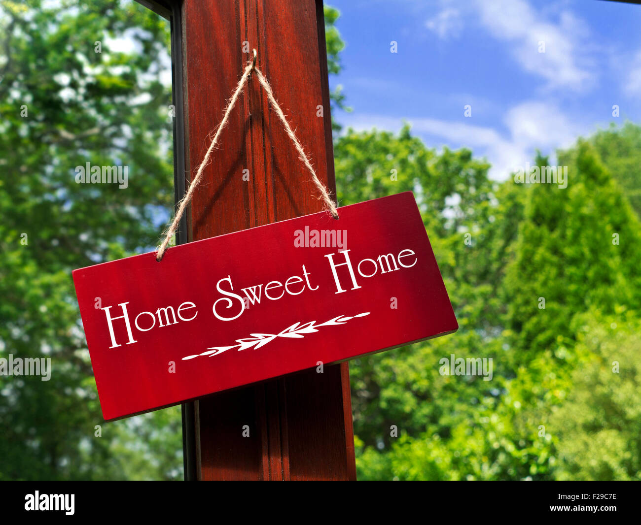 'Home Sweet Home' wooden sign hanging in a garden room with foliage and blue sky in background - Stock Image