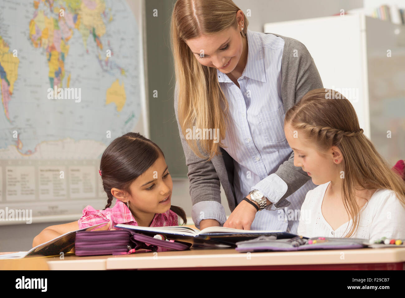 Female teacher helping students in classroom, Munich, Bavaria, Germany - Stock Image