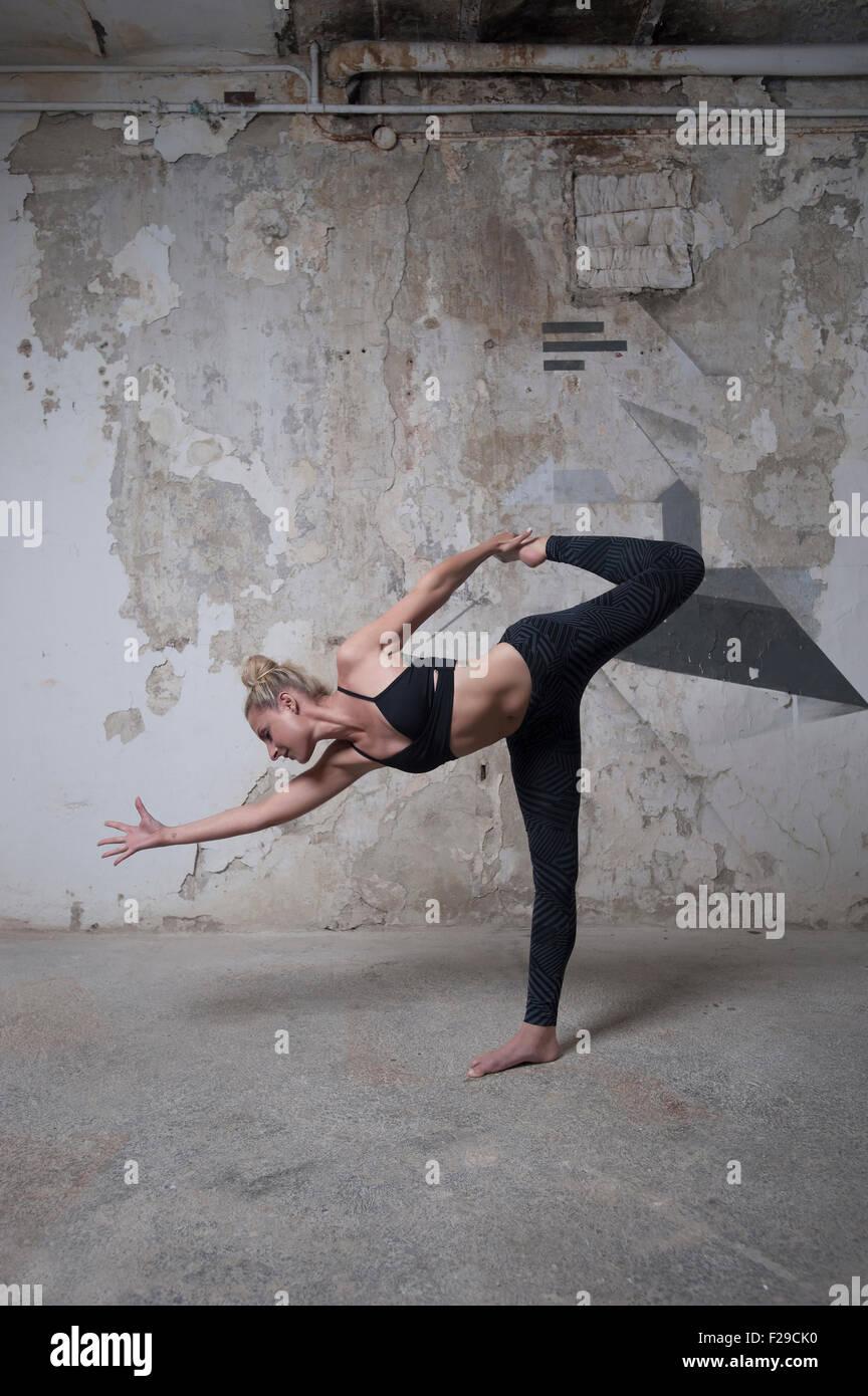 Mid adult woman practicing sugarcane pose in yoga studio, Munich, Bavaria, Germany - Stock Image