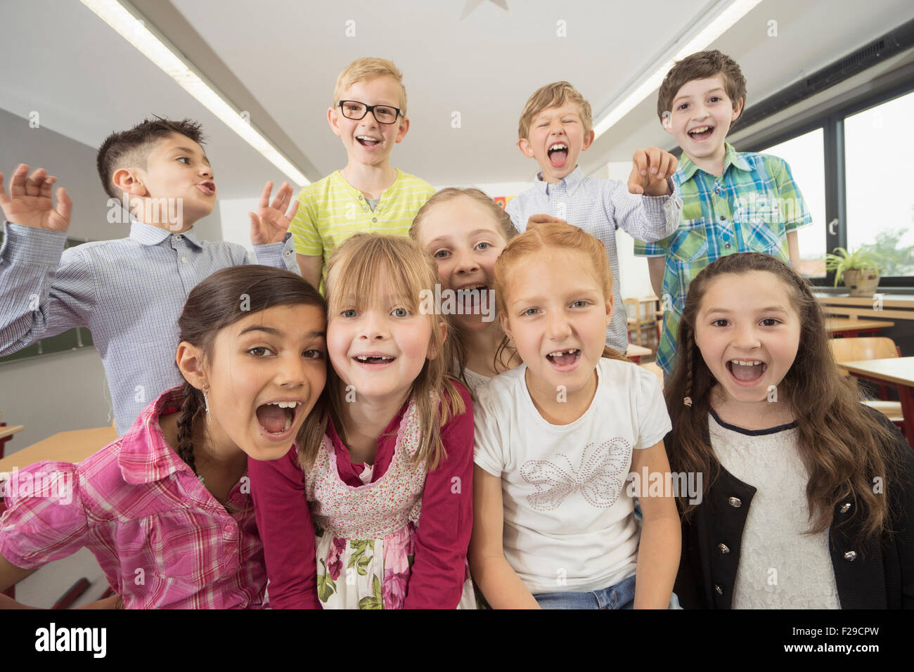 Group of schoolchildren having fun in classroom, Munich, Bavaria, Germany - Stock Image