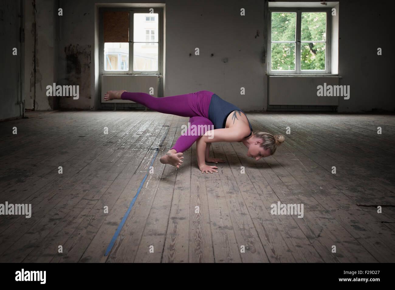 Mid adult woman practicing Eka pada koundinyasana I pose in Yoga Studio, Munich, Bavaria, Germany - Stock Image