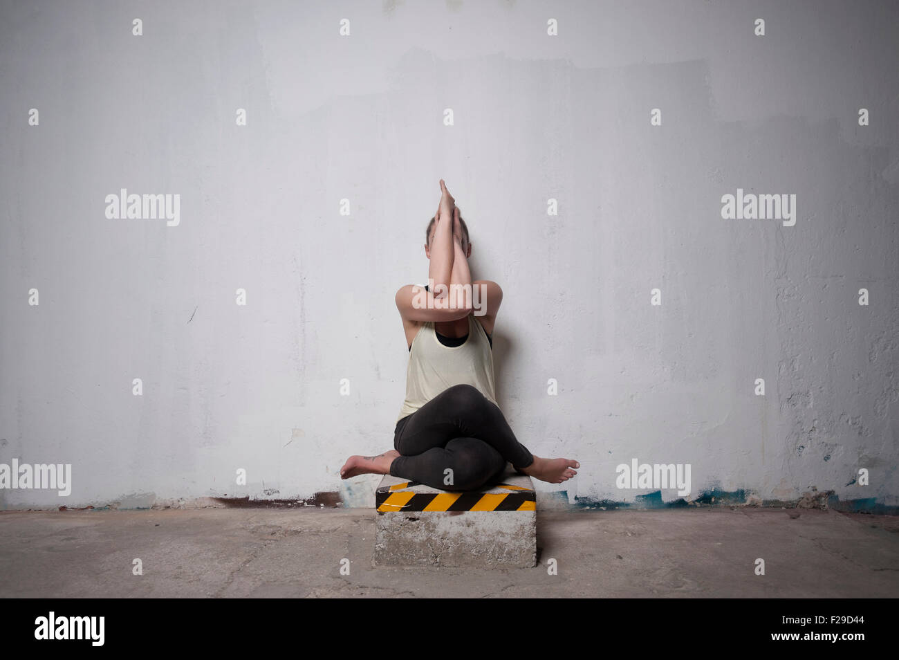 Mid adult woman practicing cow face pose in yoga studio, Munich, Bavaria, Germany Stock Photo