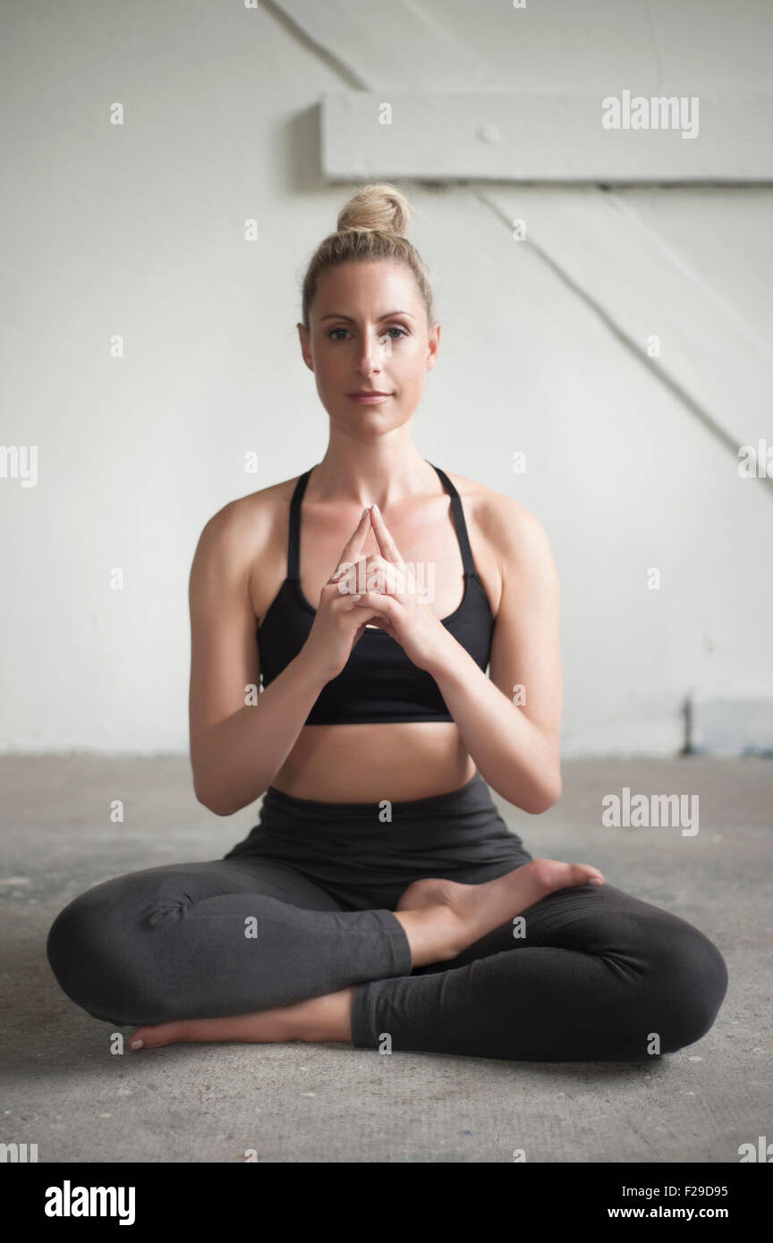 Mid adult woman meditating lotus pose in yoga studio, Munich, Bavaria, Germany - Stock Image