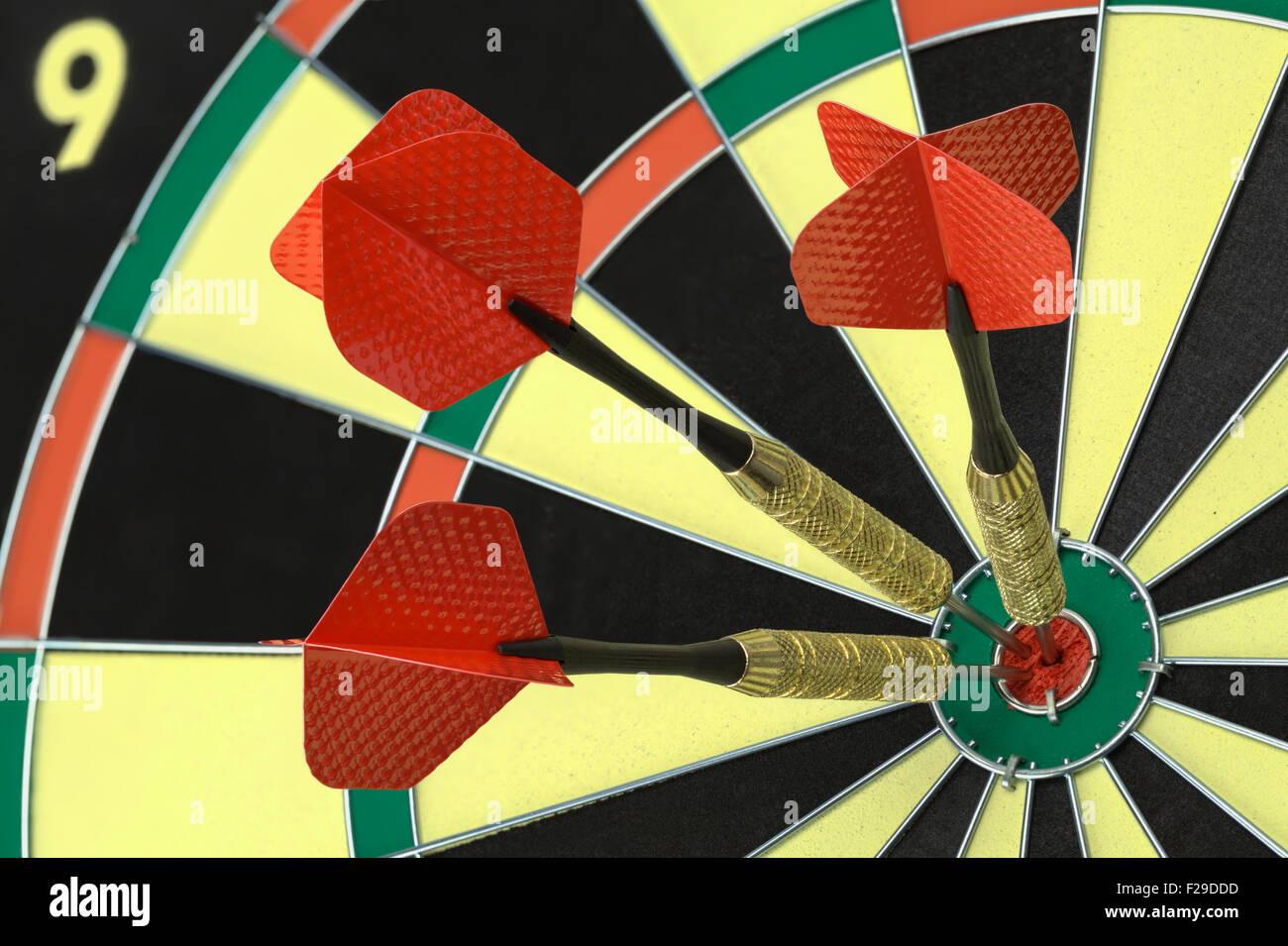 Three Darts in the Bulls Eye on Dart Board. - Stock Image
