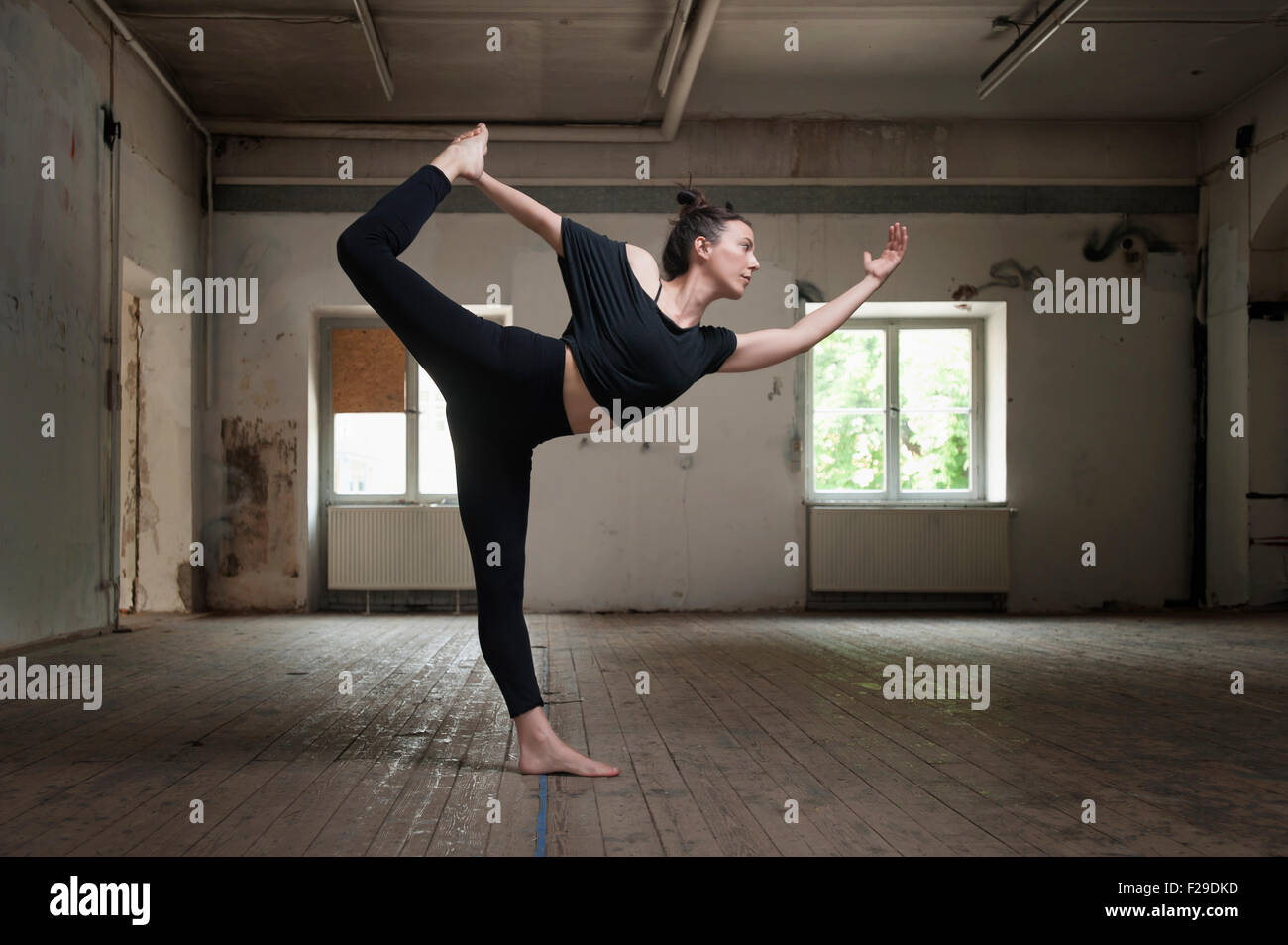 Mid adult woman practicing natarajasana pose in yoga studio, Munich, Bavaria, Germany - Stock Image