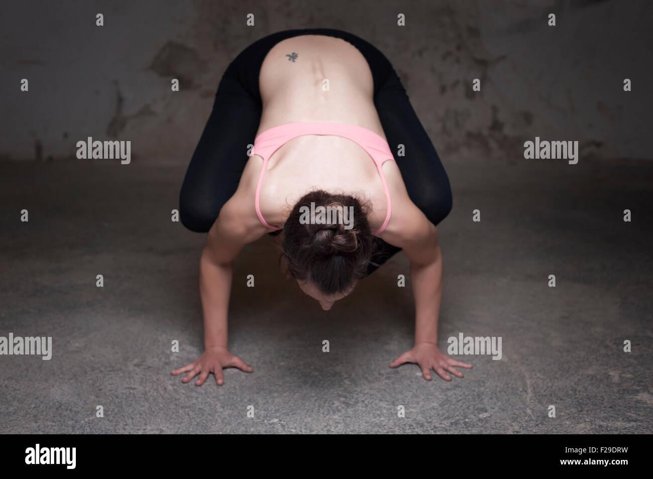 Mid adult woman practicing bakasana in yoga studio, Munich, Bavaria, Germany - Stock Image