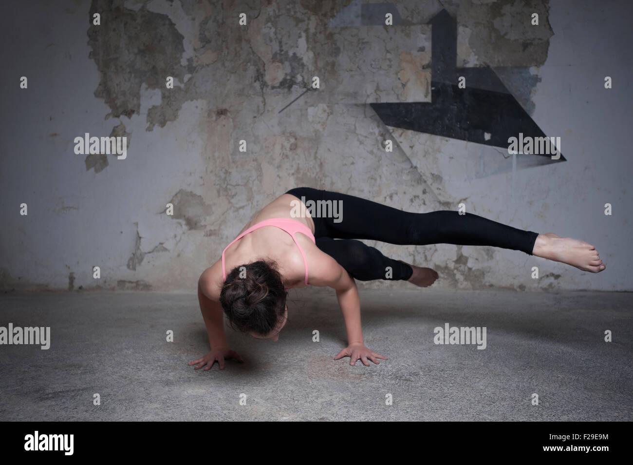 Mid adult woman practicing parsva bakasana pose in yoga studio, Munich, Bavaria, Germany - Stock Image