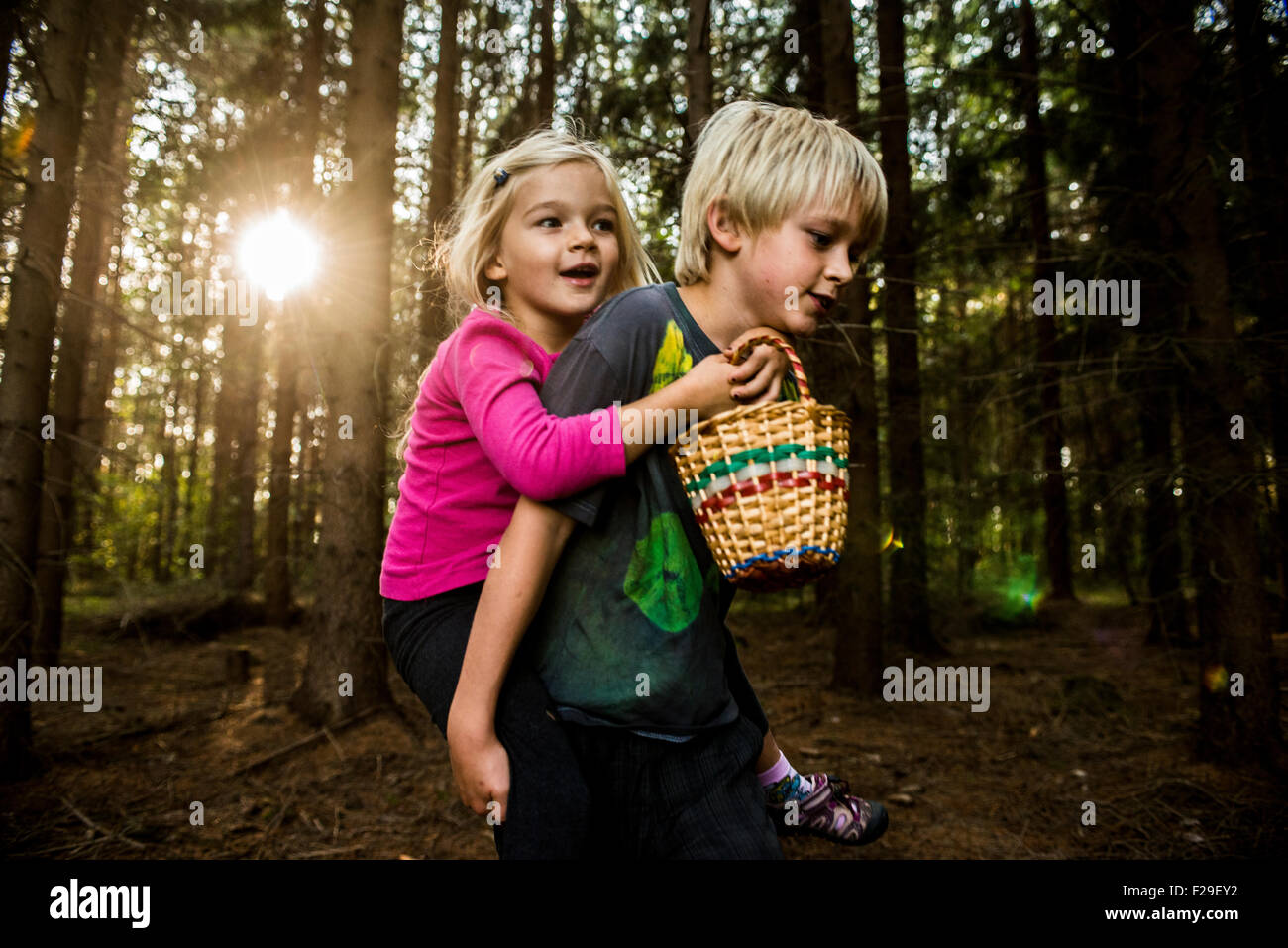 362dd0826 Young boy giving young girl piggyback outdoors smiling