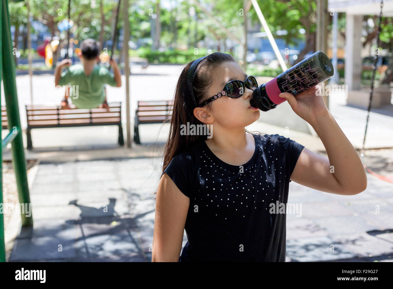 young mixed race girl drinking to cool down in the park - Stock Image