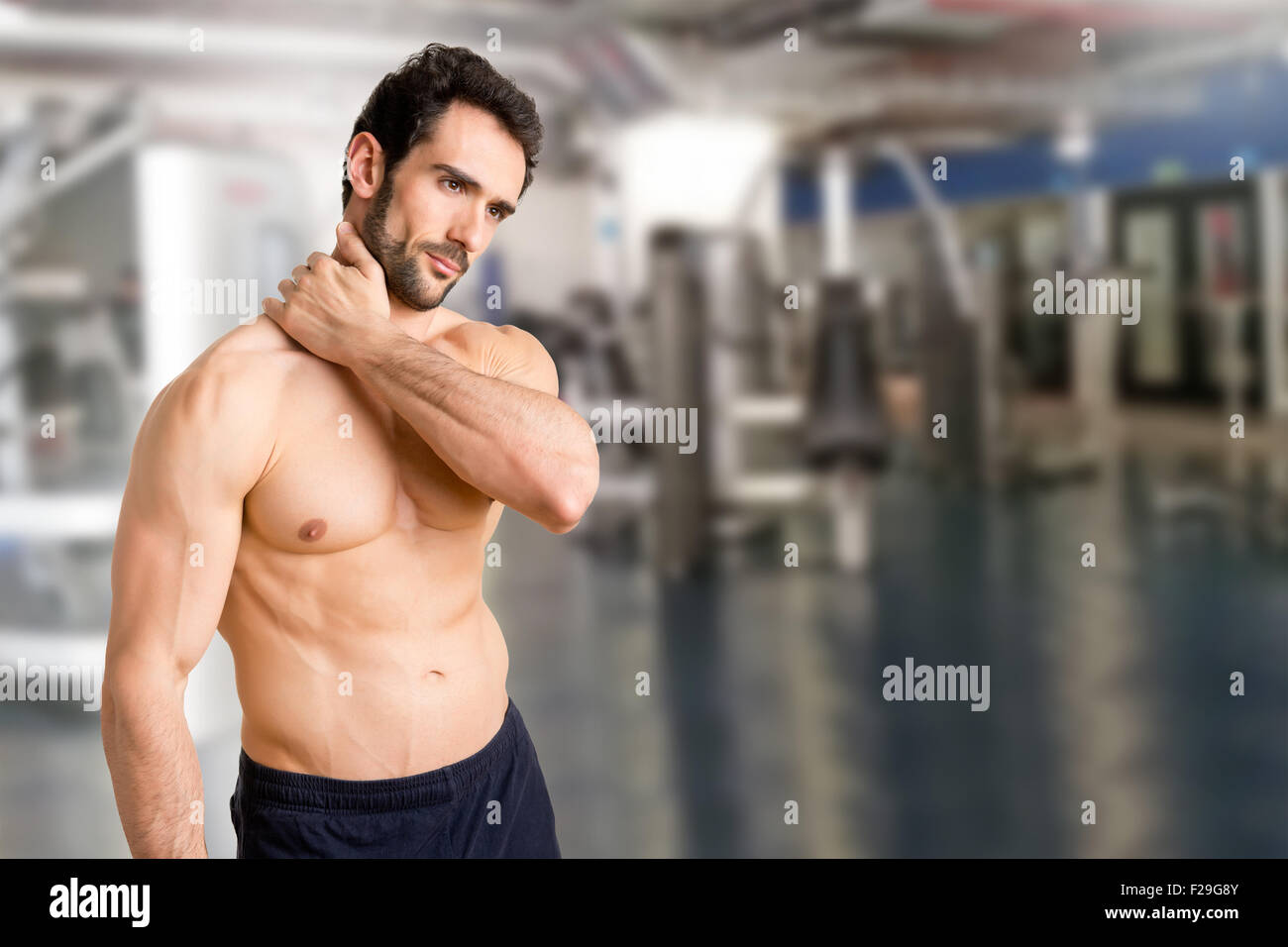 Athlete suffering from neck pain in a gym - Stock Image