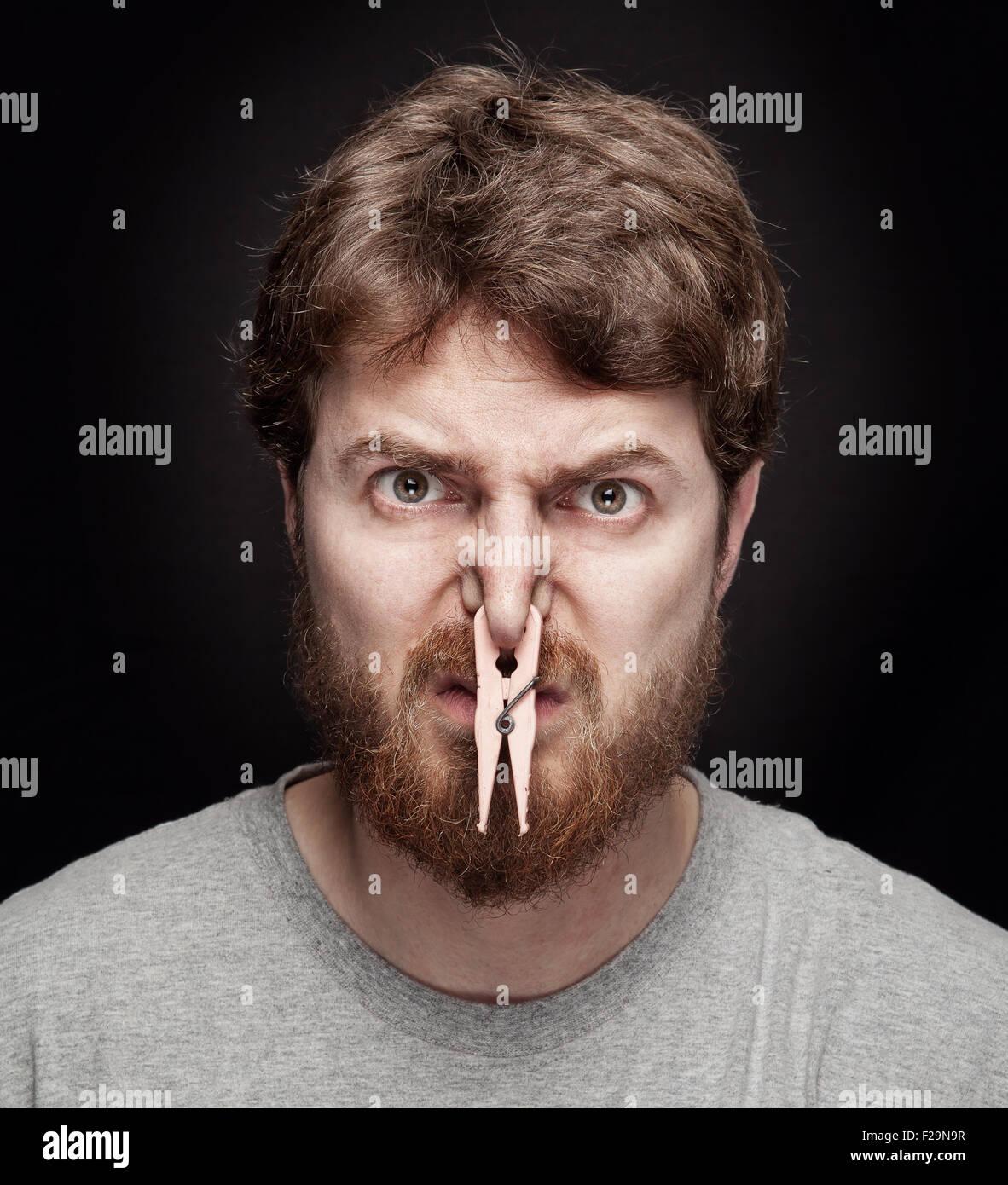 Bad smell concept - peg on male nostrils over black - Stock Image
