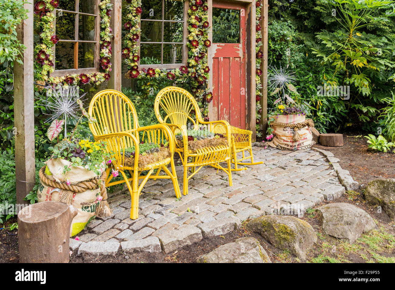 Garden display with rattan chairs as planters - Stock Image