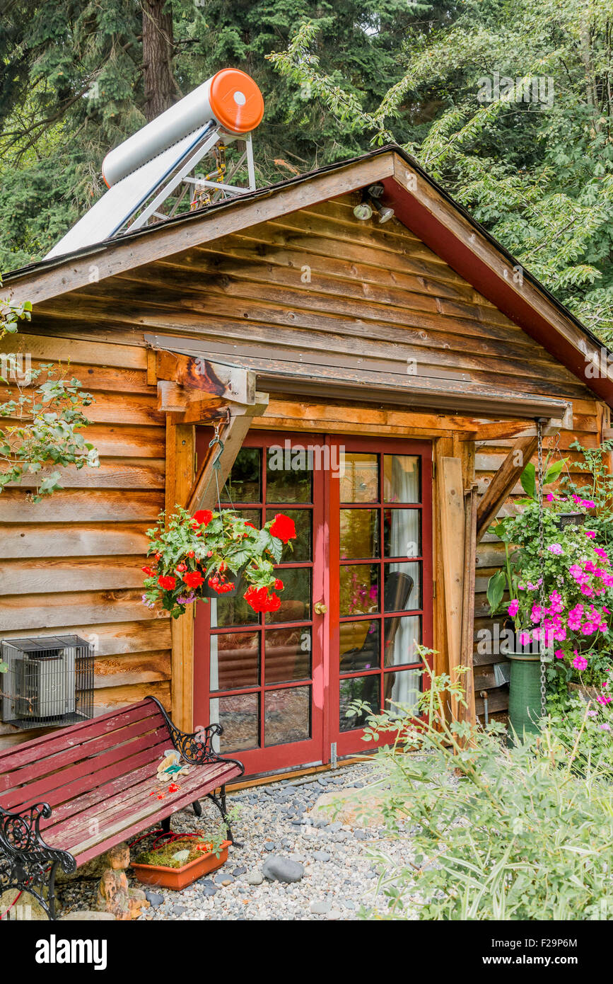 Cabin with solar water heater on roof, Sailboats, Sunshine Coast, ,British Columbia, Canada - Stock Image