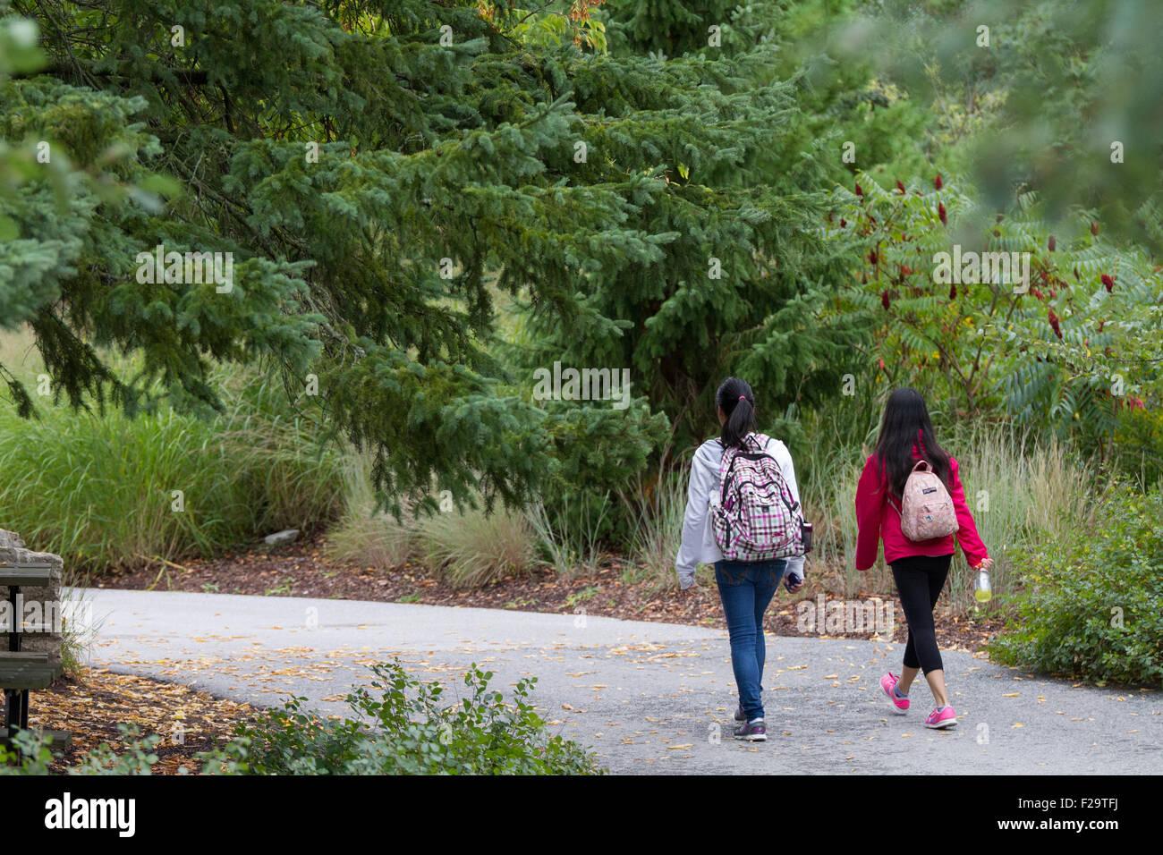 two young asian girls walking outdoor school trip back rear - Stock Image