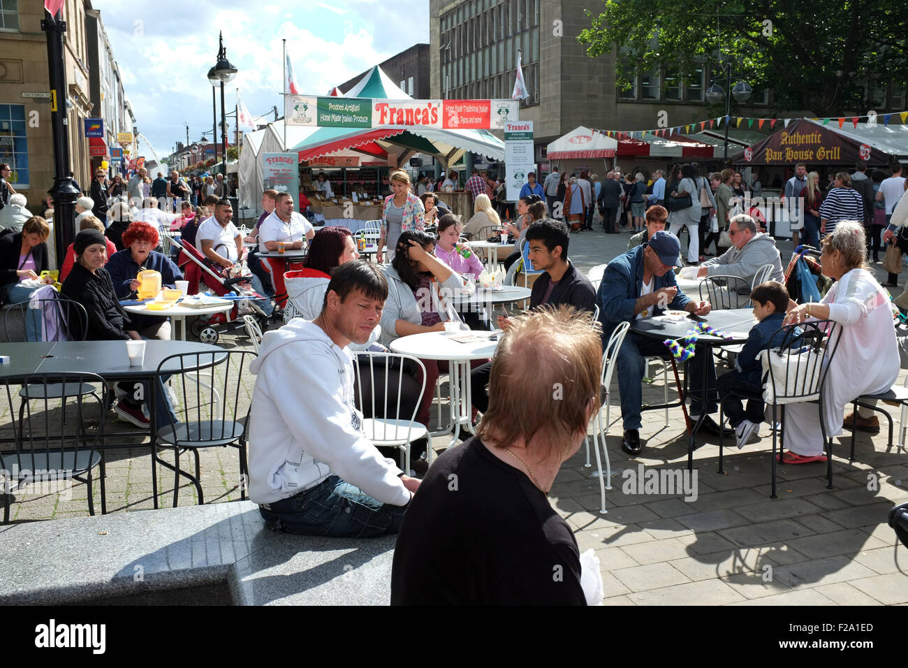 People sat in the sunshine at The Annual Bolton Food Festival on Victoria Square Bolton Town Centre, Lancashire, - Stock Image